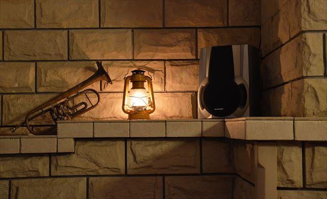 暖色照明の中に照らされた音響スピーカーとトランペットの画像
