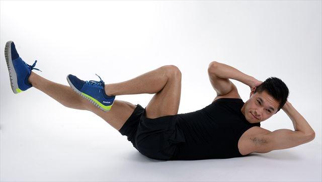 トレーニングウェアを着てストレッチ運動をする男性の画像