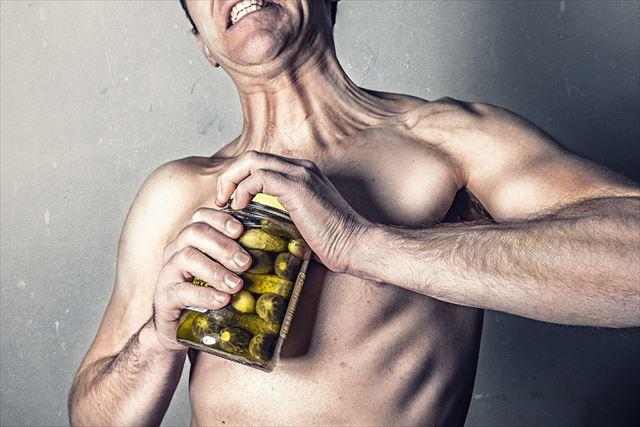 筋肉の痛みをがまんしている男性の画像